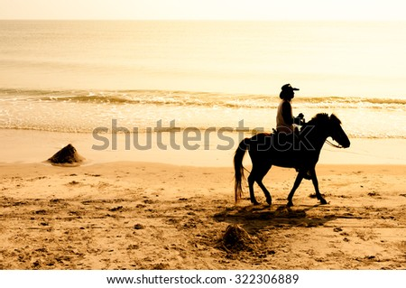 Horse riding on the beach silhouette - stock photo