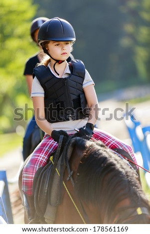 Horse riding, portrait of lovely equestrian on a horse - riding lesson - stock photo