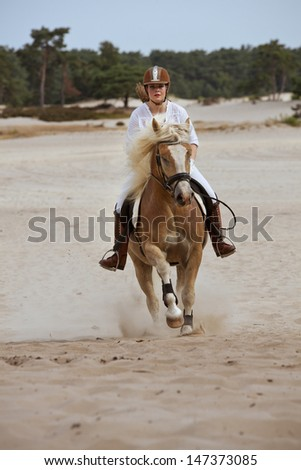 Horse riding woman in the dunes