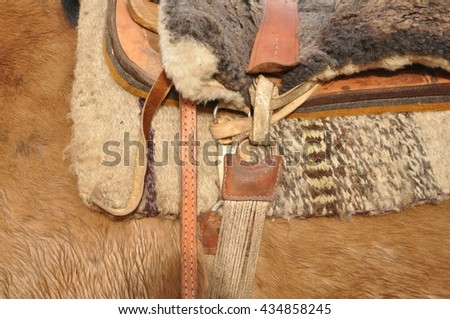 Horse saddle detail. A side detail of a horse saddle showing the cinch. - stock photo