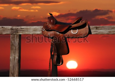 Horse saddle on rural fence - stock photo