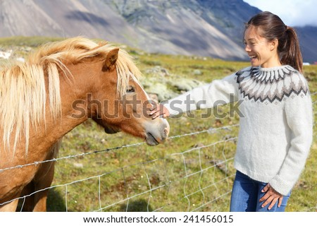 Horse - woman petting Icelandic horses in sweater on Iceland. Happy smiling girl going horseback riding. - stock photo