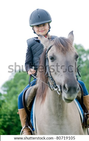 Horseback riding - little girl is riding a horse - stock photo
