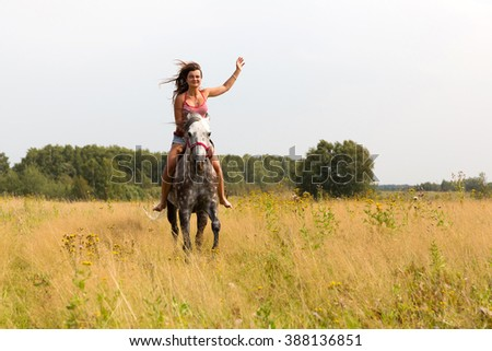 Horseback riding, lovely equestrian - girl is riding a horse - stock photo