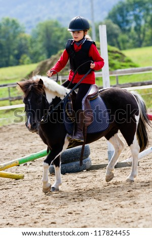 Horseback riding, lovely equestrian - young girl is riding a pony - stock photo