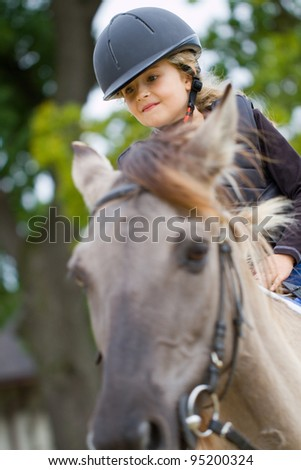 Horseback riding - lovely girl is riding a horse - stock photo