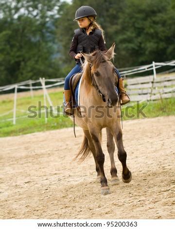 Horseback riding - lovely girl is riding a horse - stock photo