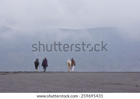 Horseman and their horse walking at desert place with foging environment - stock photo