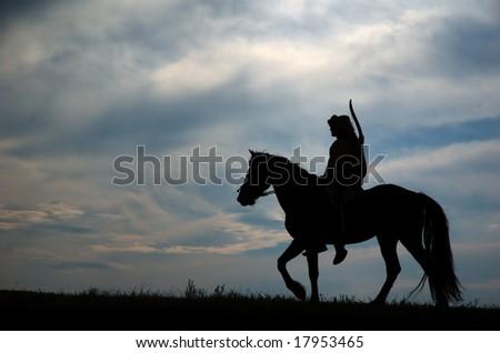 Horsemen riding on the sunset - stock photo