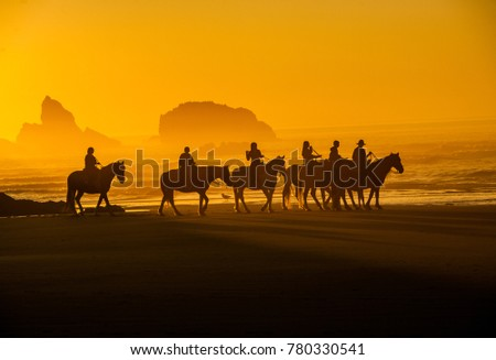 Horses and riders (riding in front of sea stacks) on the beach at sunset on the sougern Oregon coast at Bandon