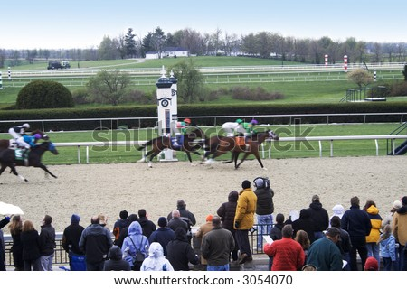 Horses crossing the finish line in a close race at Keenland RAce track in Lexington, Kentucky - stock photo
