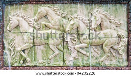 Horses in low relief statue cut out as jig saw image and water fall in front of. - stock photo