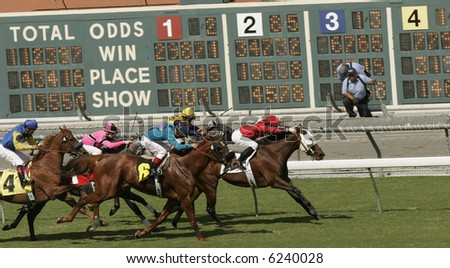 Horses Race Past the Tote Board - stock photo