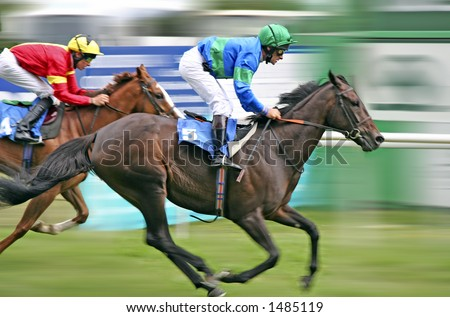 Horses racing at speed with blurred background - stock photo