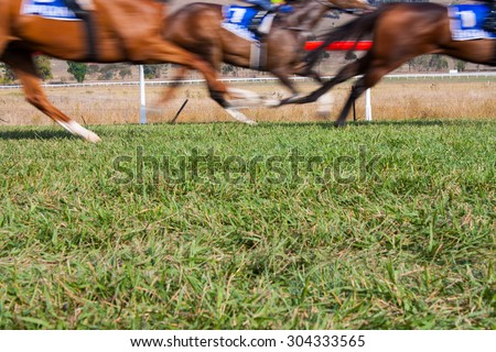 Horses running past on the racetrack - stock photo