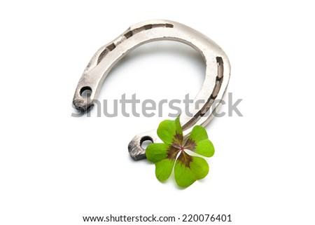 Horseshoes and clover with four leaf on white background - stock photo
