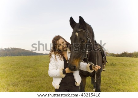 Horsewoman holds the horse's bridle. - stock photo