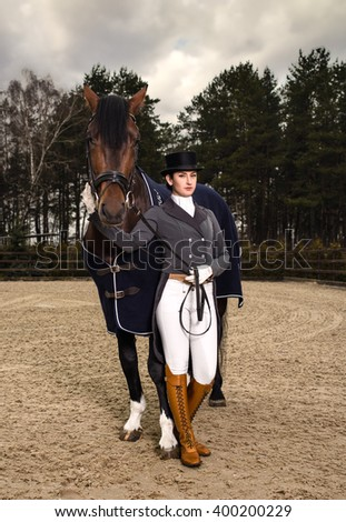 Horsewoman in uniform with a brown horse outdoor - stock photo
