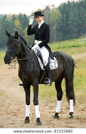 horsewoman jockey in uniform riding horse outdoors - stock photo