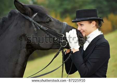 horsewoman jockey in uniform standing with horse outdoors - stock photo