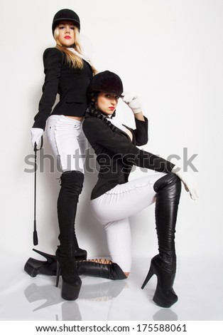 Horsewomans.Two attractive sexy girls posing in fetish outfits. Studio shot - stock photo