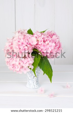 Hortense in old cracked  vase on wooden board in shabby chic style - stock photo