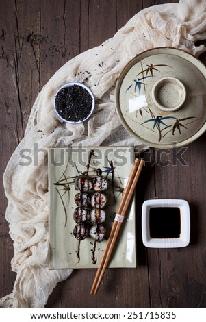 hosomaki sushi on plate with soy sauce, bowl and sesame seeds on table - stock photo