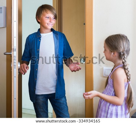 Hospitable russian child receiving expected friend at home interior. focus on boy - stock photo