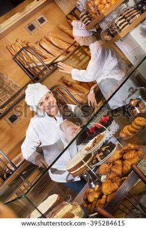 Hospitable women with delicious cream pies at bakery display  - stock photo