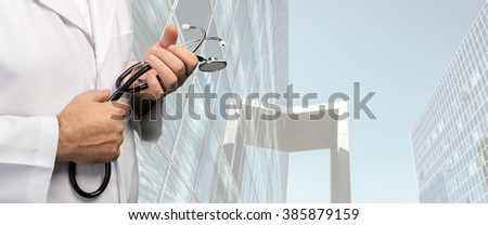 Hospital, doctor and health care concept. Close up image of a medical doctor hands with a stethoscope against blurred hospital background - stock photo