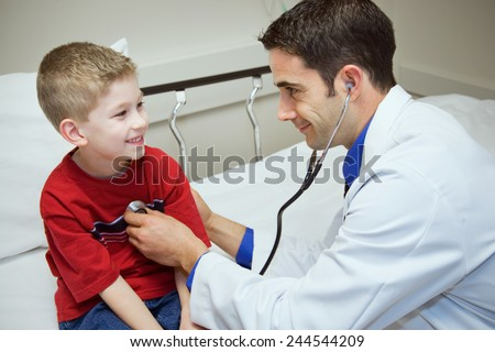 Hospital: Doctor Checks Heartbeat Of Young Boy - stock photo