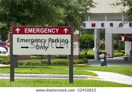 Hospital emergency entrance sign giving directions to emergency parking - stock photo