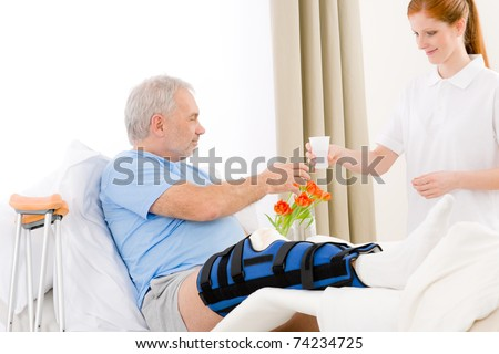 Hospital - female nurse give drink to patient with broken leg - stock photo