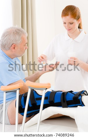 Hospital - female nurse give pill patient with broken leg - stock photo