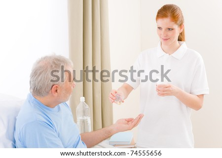 Hospital - female nurse give pill to senior patient - stock photo