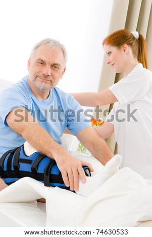 Hospital - female nurse take care of patient with broken leg - stock photo