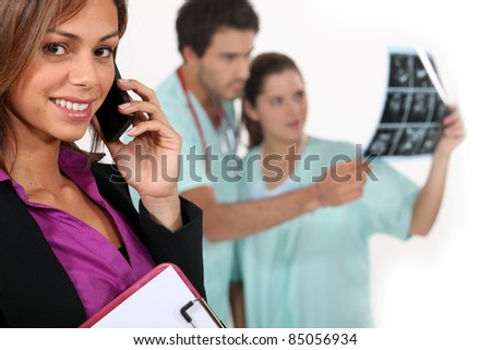 Hospital manager on a phone as medics look at x rays in the background - stock photo
