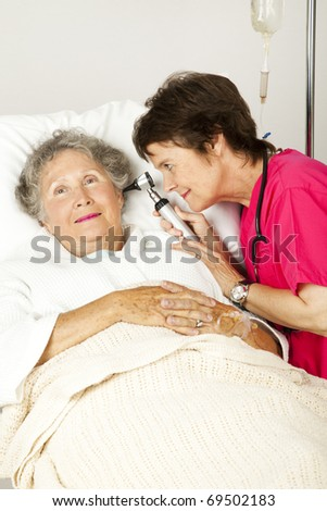 Hospital nurse checking a senior woman patient's ears with an otoscope.