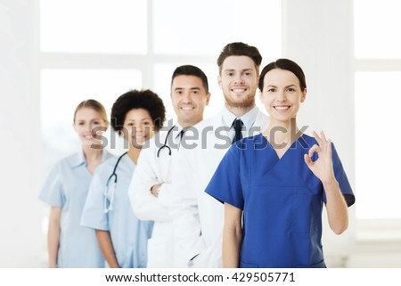 hospital, profession, gesture, people and medicine concept - group of happy doctors showing ok hand sign at hospital - stock photo