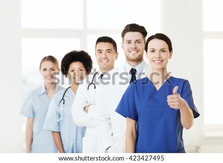hospital, profession, gesture, people and medicine concept - group of happy doctors showing thumbs up at hospital