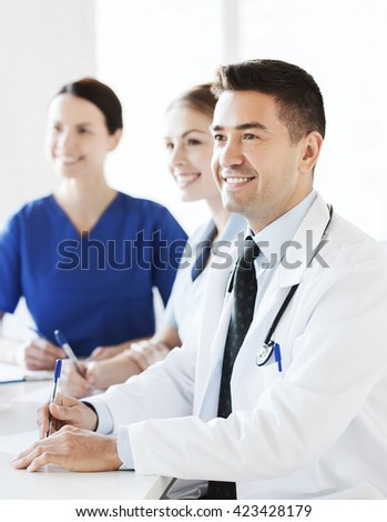 hospital, profession, medical education, people and medicine concept - group of happy doctors meeting on presentation at hospital - stock photo