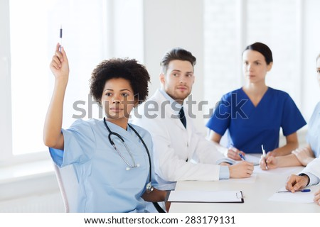 hospital, profession, people and medicine concept - group of happy doctors meeting and asking questions on conference at hospital - stock photo