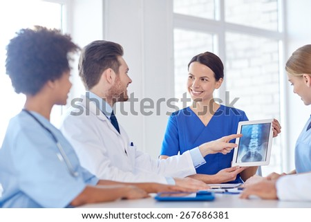 hospital, profession, people and medicine concept - group of happy doctors with tablet pc computers meeting at medical office - stock photo