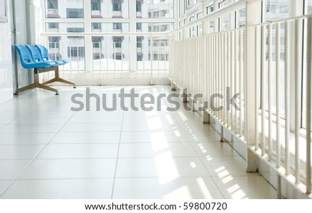 Hospital waiting room with empty blue chairs. - stock photo