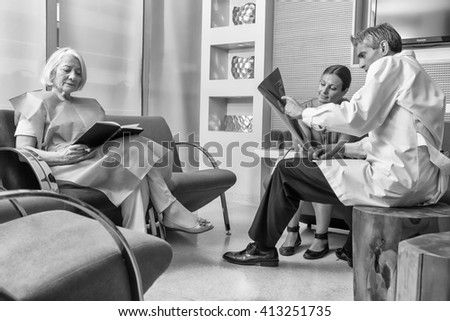 Hospital waiting room with patients and doctor. - stock photo