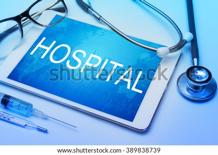 Hospital word on tablet screen with medical equipment on background - stock photo