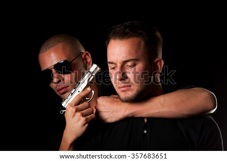 Hostage - a dangerous man with a gun kidnapping a businessman - stock photo