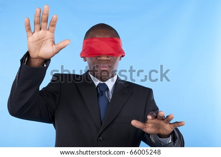Hostage african businessman with a red blindfold covering his eyes - stock photo