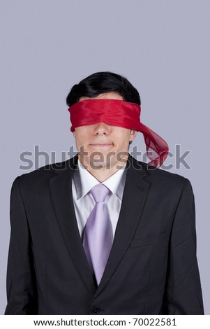 Hostage businessman with a red blindfold covering his eyes (isolated on gray) - stock photo