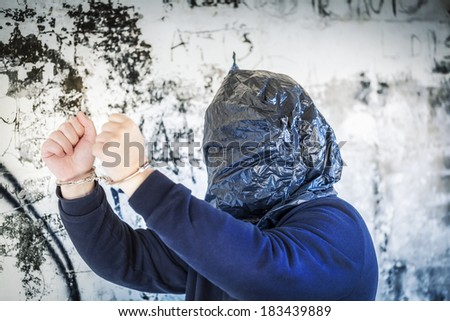 Hostage in handcuffs and with a bag on head near wall  - stock photo